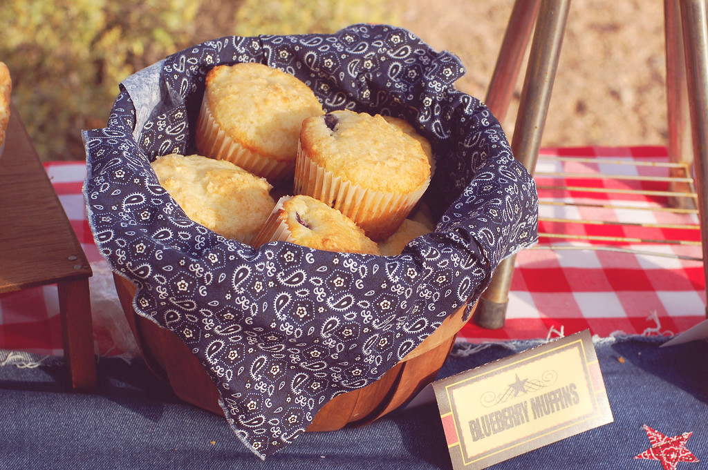 Blueberry muffins in a wooden basket lined with navy blue and white paisley print fabric on a red and white checked tablecloth.