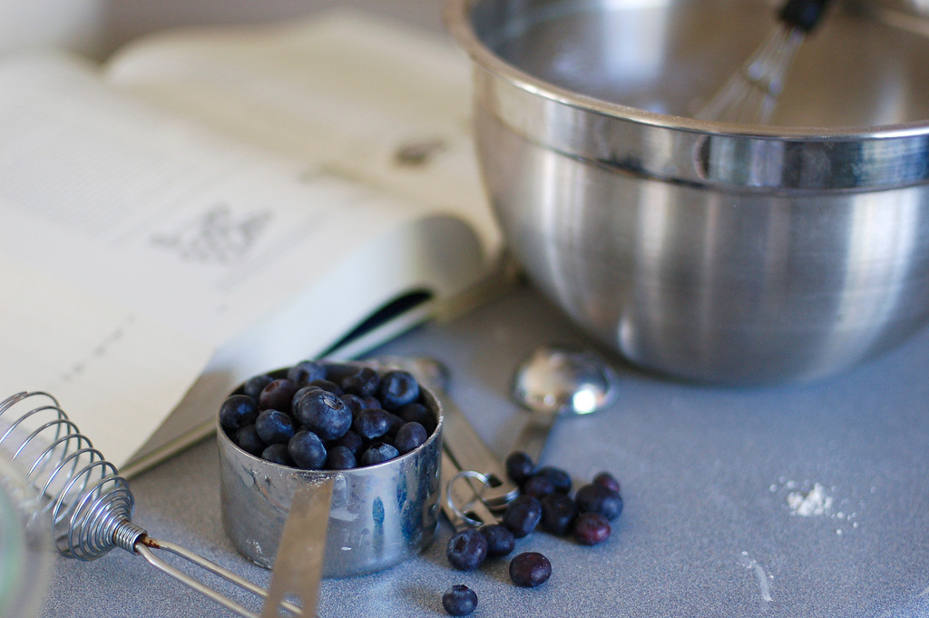 Cup of fresh blueberries on table next to cookbook and silver bowl and egg beater and measuring spoons.