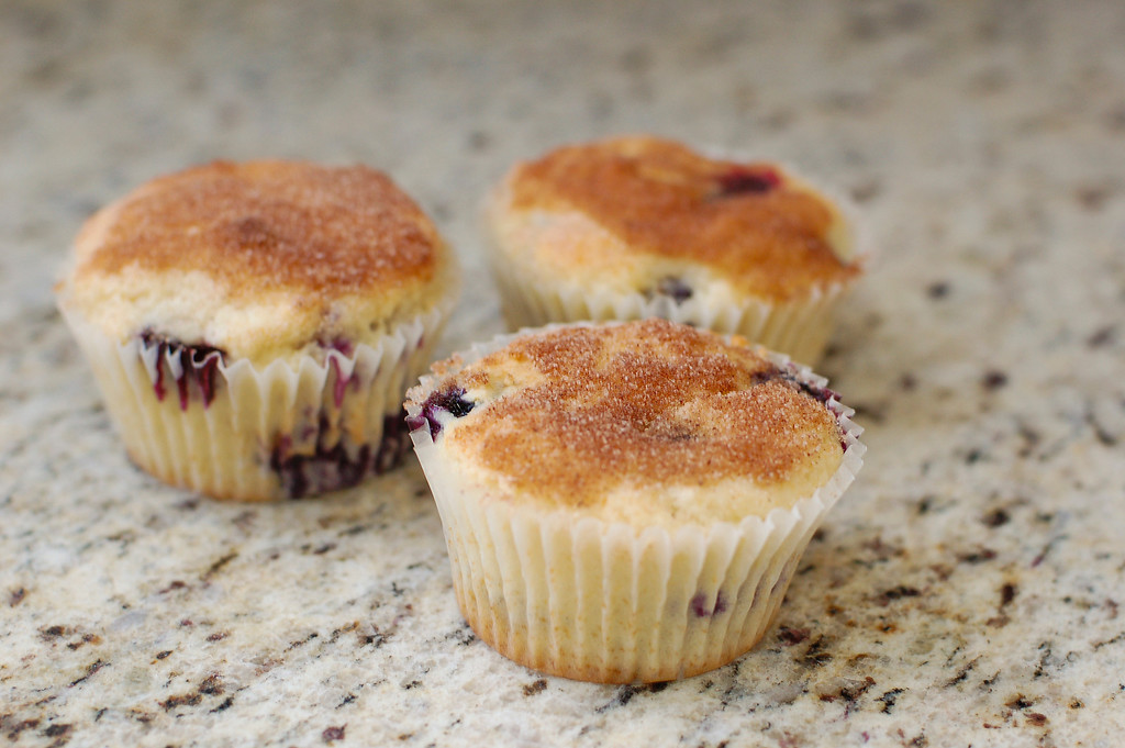 Three blueberry muffins on a granite countertop